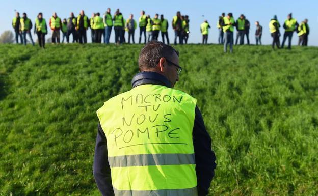 Un hombre usa un chaleco amarillo que dice «Macron nos bombea».